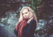 Porträt einer Frau mit dem blonden gelockten Haar auf dem Hintergrund des Winterwaldes Stockfoto