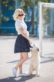 Porträt einer Frau mit dem schönen Hund, der draußen spielt Stockfoto