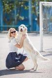 Porträt einer Frau mit dem schönen Hund, der draußen spielt Stockbild