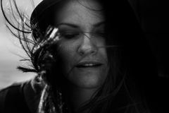 Porträt einer Frau mit dem windigen schwarzen Haar in einer Haube, bnw Foto stockfotos