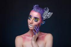 Porträt einer Frau mit kreativem Make-up auf einem blauen Hintergrund Lizenzfreies Stockbild