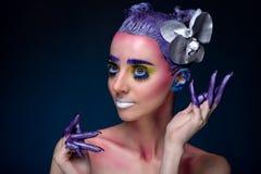 Porträt einer Frau mit kreativem Make-up auf einem blauen Hintergrund Stockfotos
