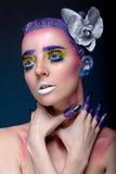 Porträt einer Frau mit kreativem Make-up auf einem blauen Hintergrund Stockbilder