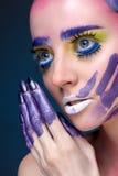 Porträt einer Frau mit kreativem Make-up auf einem blauen Hintergrund Stockfoto