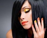 Porträt einer Frau mit roten Nägeln und Zaubermake-up lizenzfreies stockbild