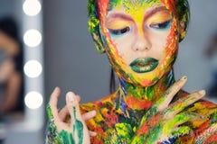 Porträt einer Frau vollständig bedeckt mit starker Farbe stockfotografie