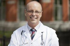 Porträt einer freundlichen Kamera Doktor-Smiling At The Stockbild