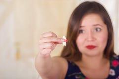 Porträt einer furchtsamen Frau, die in ihrer Hand eine vaginale Tablette der weichen Gelatine oder ein Zäpfchen, Behandlung von K Lizenzfreie Stockfotografie