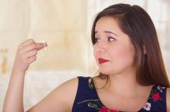 Porträt einer furchtsamen Frau, die in ihrer Hand eine vaginale Tablette der weichen Gelatine oder ein Zäpfchen, Behandlung von K Stockfoto