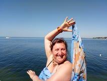 Porträt einer gebräunten Frau, die auf einem Pier hält ein pareo steht Stockbilder