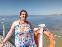 Porträt einer gebräunten Frau, die auf einem Pier steht Lizenzfreie Stockfotos