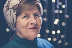 Porträt einer geknitterten netten Großmutter des Gesichtes in einem Kopftuch mit bokeh Stockfotos