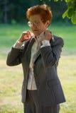 Porträt einer Geschäftsfrau alterte, eine Klage korrigierend Stockfoto