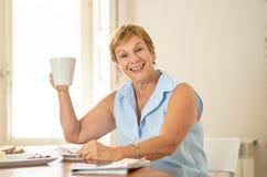 Porträt einer glücklichen älteren Frau, die Morgenkaffee trinkt stockfotografie