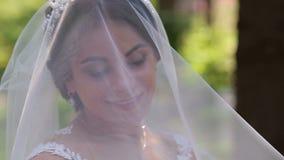 Porträt einer glücklichen Braut in einem Schleier mit einem umfassten Kopf in einem Sommerpark stock video