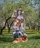 Porträt einer glücklichen Familie auf einem Schwingen in ihrem Garten lizenzfreies stockfoto