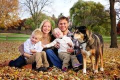 Porträt einer glücklichen Familie des Mutter-Vaters und zwei Kinder und ihres Hundes auf Autumn Day lizenzfreie stockfotos