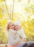Porträt einer glücklichen Familie mit schöner blonder Mutter und kleinen der Tochter, die im Park stillsteht Lizenzfreie Stockfotos