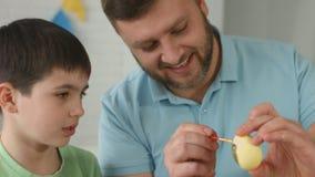 Porträt einer glücklichen Familie, Vater und Sohn, die Eier auf Ostern malen stock footage