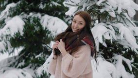 Porträt einer glücklichen Frau, die mit ihrem Haar im Winterwald geht, die Dame wirft nahe bei einem schneebedeckten Baum auf stock video