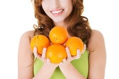Porträt einer glücklichen Frau, die Orangen hält Stockfotos