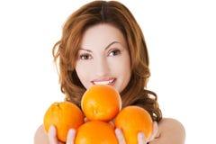 Porträt einer glücklichen Frau, die Orangen hält stockbilder