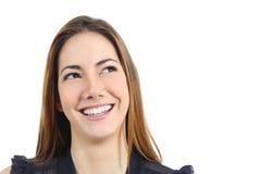 Porträt einer glücklichen Frau mit dem perfekten weißen Lächeln, das seitlich schaut Stockbilder