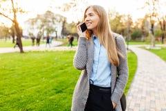Porträt einer glücklichen Frau, stehend im Park und sprechen auf lizenzfreie stockfotografie