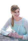 Porträt einer glücklichen jungen Frau, die ein Getränk a genießt Lizenzfreies Stockbild