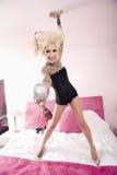 Porträt einer glücklichen jungen Frau, die Mikrofon bei der Stellung auf Bett gibt Stockfoto