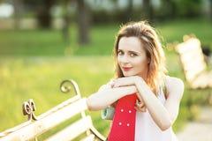 Porträt einer glücklichen lächelnden jungen Frau mit einem rosa Skateboard stockbild