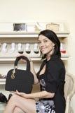 Porträt einer glücklichen mittleren erwachsenen Frau, die Designergeldbeutel im Schuhgeschäft zeigt Lizenzfreie Stockbilder