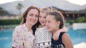 Porträt einer glücklichen Mutter mit zwei Töchtern auf dem Hintergrund des Pools stock footage