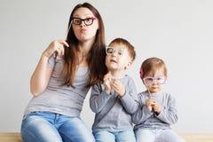 Porträt einer glücklichen Mutter und ihrer Kinder gegen eine Weißrückseite lizenzfreies stockfoto