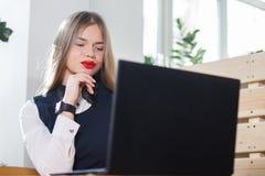 Porträt einer glücklichen zufälligen Geschäftsfrau in der Strickjacke, die an ihrem Arbeitsplatz im Büro sitzt Stockfoto