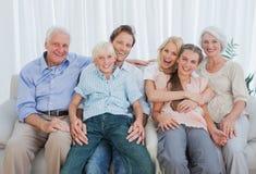 Porträt einer Großfamilie, die auf Couch sitzt Stockbilder