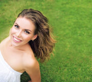 Porträt einer hübschen Frau, die auf dem frischen Rasen sich entspannt Stockfotos