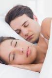 Porträt einer hübschen Frau, die nahe bei ihrem Partner schläft Stockbild