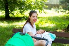 Porträt einer hübschen stillende Mutter und des Babys, junge Mutter ist draußen mit ihrem neugeborenen Kind für Spaziergängerweg, Stockfoto