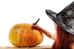Porträt einer Hexe mit dem roten Haar, das auf einen Kürbis zeichnet Lizenzfreie Stockbilder