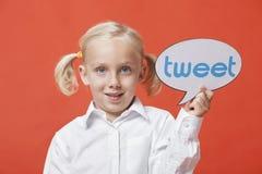 Porträt einer Holdingtweetblase des jungen Mädchens gegen orange Hintergrund Lizenzfreie Stockfotos