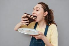 Porträt einer hungrigen schwangeren Frau, die Kuchen der süßen Schokolade isst stockbilder
