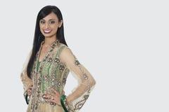 Porträt einer indischen Frau in der eleganten Designerabnutzung, die mit den Händen auf Hüften über grauem Hintergrund steht Stockfoto