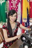 Porträt einer indischen weiblichen Damenschneiderin, die Nähmaschine verwendet stockfotografie