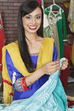 Porträt einer indischen weiblichen Damenschneiderin, die Sari hält lizenzfreie stockbilder