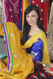Porträt einer indischen weiblichen Damenschneiderin, die Sari hält lizenzfreie stockfotos