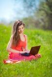 Porträt einer intelligenten jungen Frau, die auf Gras liegt und Laptop verwendet Stockbild