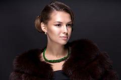 Porträt einer Jugendlichen in einem Pelzmantel auf einem dunkelgrauen backgrou Stockfotos