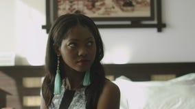 Porträt einer jungen afro-amerikanischen Frau mit dem dunklen Haar, das auf einem Sofa in einem stilvollen Hotelzimmer sitzt stock footage