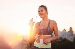 Porträt einer jungen attraktiven Frau in der Sportkleidung, hörend auf Lizenzfreie Stockfotos